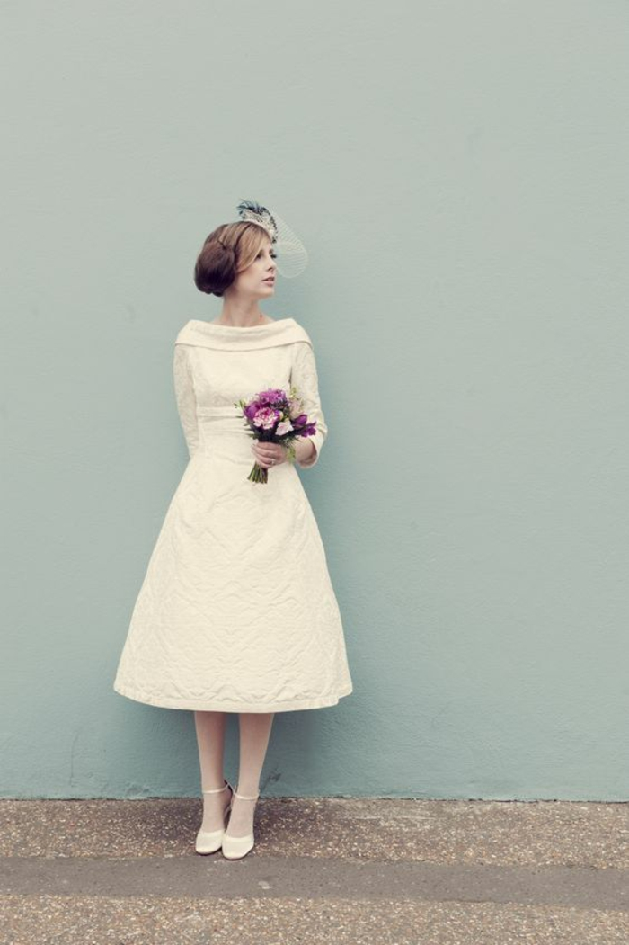 short white wedding dresses, woman in plain white calf-length dress and a head ornament, wearing white sheer tights and white shoes with straps, holding a bouquet of violet flowers, light blue and brown background