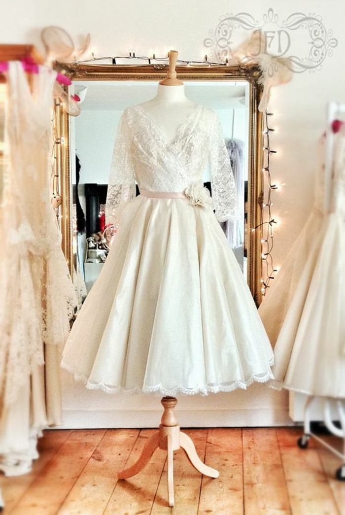 short lace wedding dress, dress with lace top and pink belt with flower, sheer sleeves and plain bottom, on a simple wooden mannequin, in front of a mirror with fairy lights in a room with other white dresses
