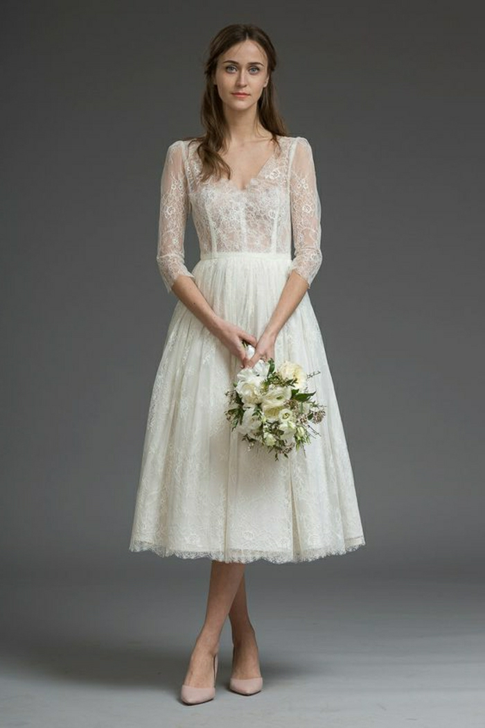 short lace wedding dress, bride with loose brown hair, wedding a white and cream wedding dress with lace and nude shoes, holding a white and green bouquet, on a grey background