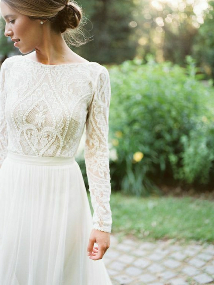 semi close-up of a blonde bride in a white dress with embroidered top and plain bottom, with a simple hair knot, trees and bushes in background