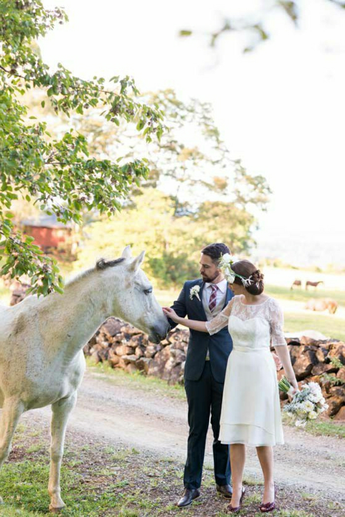 short white wedding dresses, bride in white knee-length dress with lace details and a head ornament with white flowers, holding a bouquet and a groom in black suit and red-striped tie petting a white horse near a field and trees