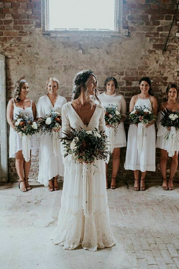 simple wedding dress, smiling bride in white long bohemian hippie dress holding a large green and white bouquet, five bridesmaids in white dresses holding flowers in background, old brick shabby interior