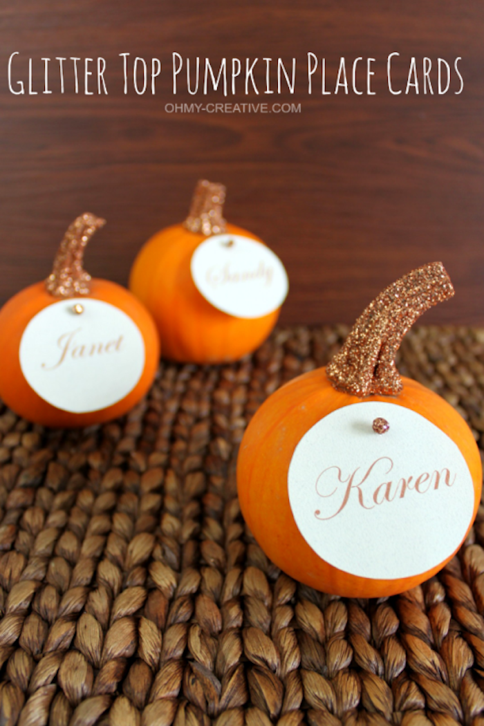three small orange pumpkins, stems painted with glittering golden paint, with round name tags attached with a pin, on a rough fabric surface, wooden background with white writing