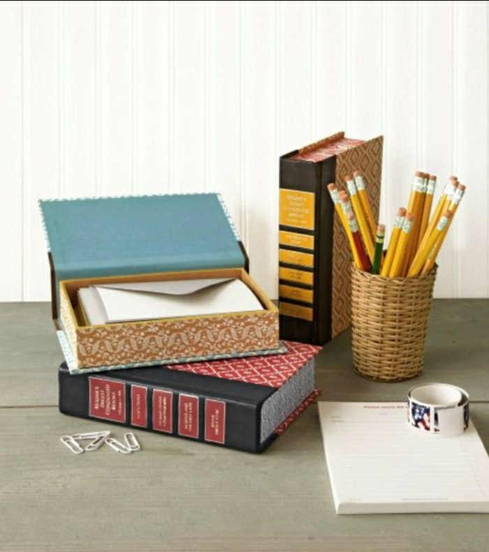 old books turned into stationary boxes, on a wooden table, near a pencil case, paper clips and a note pad