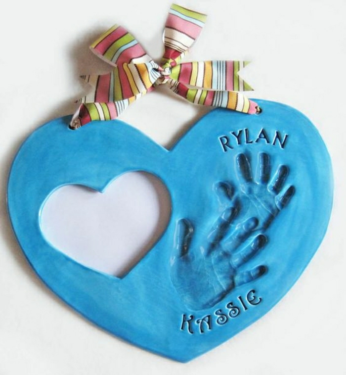 a blue plaster heart, tied with a colorful bow, with children's handprints and names inside
