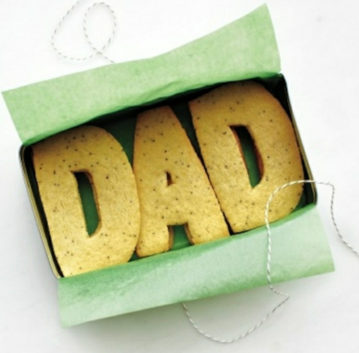 "letter-shaped cookies spelling ""dad"", in a box with a striped string, green wrapping paper"