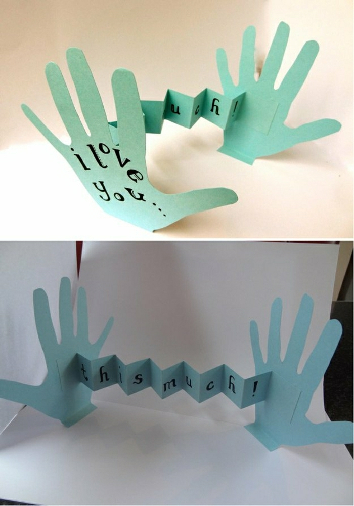 "step dad gift ideas, card made from kid's traced hands, which can be unfolded to show the message ""I love you this much"", green-blue paper, black writing, light background"