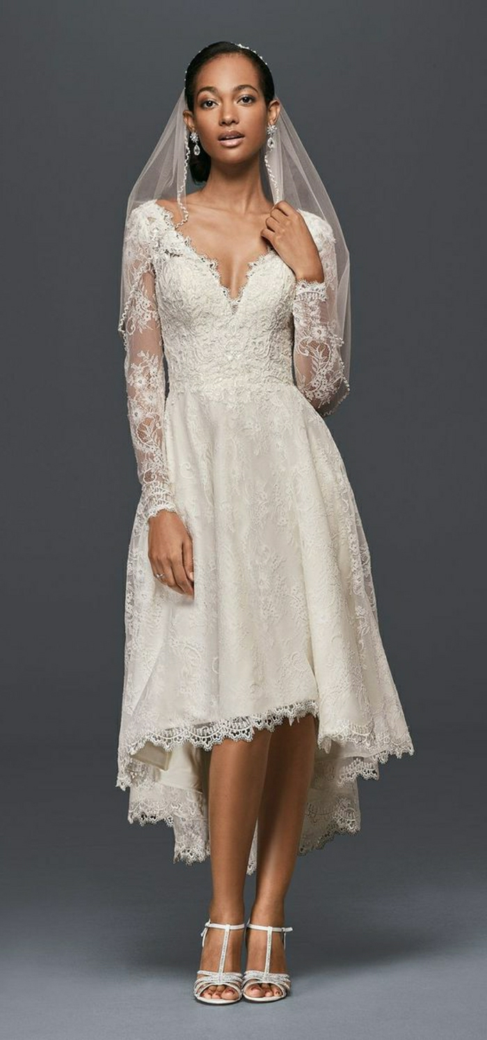 short lace wedding dress, african-american bride wearing a calf-length dress with lace and long sheer lace sleeves, with white sandals and a sheer veil on dark grey background