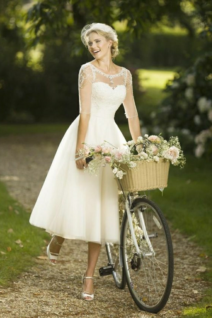 tea length wedding dresses, smiling bride in calf-length white dress with sheer sleeves pushing a bike with a flower basket
