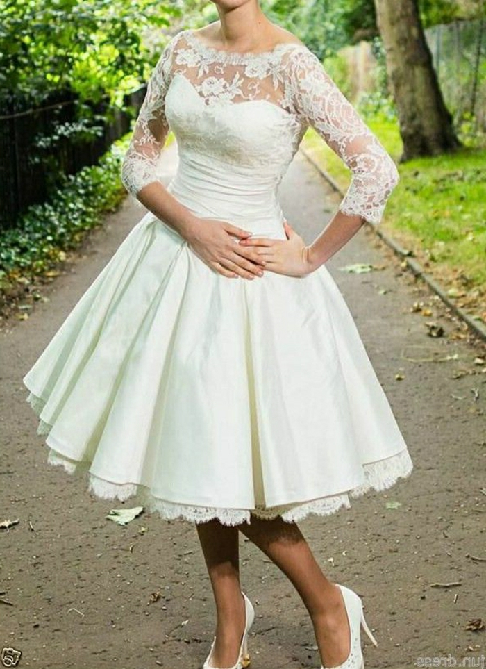 tea length dresses, close up of a woman's body in white calf-length bridal dress with lace details and sheer sleeves, hands on stomach and hips and wearing white shoes, park in background