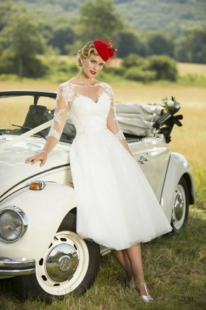 tea length dresses, bride with vintage 1950s dress red cap and silver shoes, leaning on an old white convertible car decorated with white bow, green fields and trees