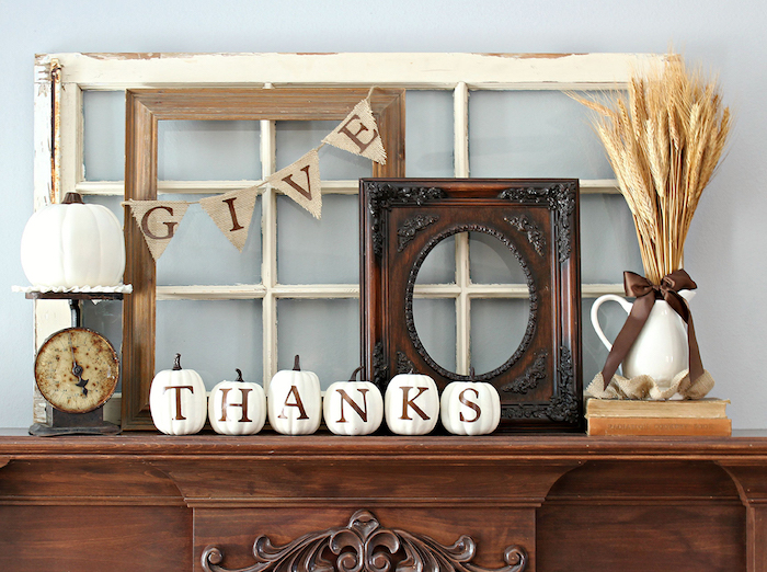 thanksgiving photos, a wooden carved mantle, with five little white pumpkins spelling out thanks in brown letters, a milk jug placed on two books, with a bunch of wheat tied with a brown ribbon in it, three wooden frames in different colors with a banner saying give, a bigger white pumpkin and decorations