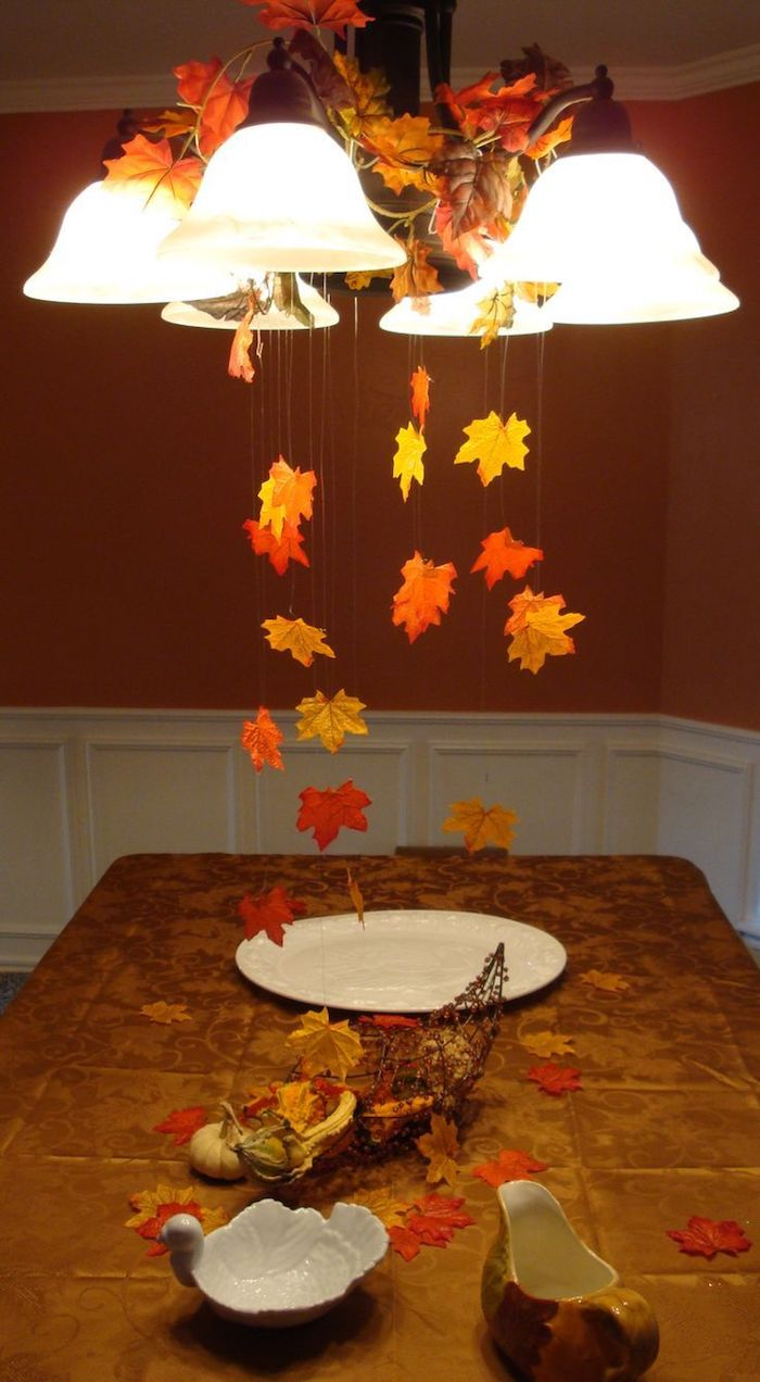 thanksgiving pics, yellow and orange leaves, hanging on strings, from a lit chandelier, over a brown kitchen table, with s white plate, gravy jug, swan shaped bowl, and a cornucopia wire ornament with small pumpkins, gourds and autumn leaves, white and dark background