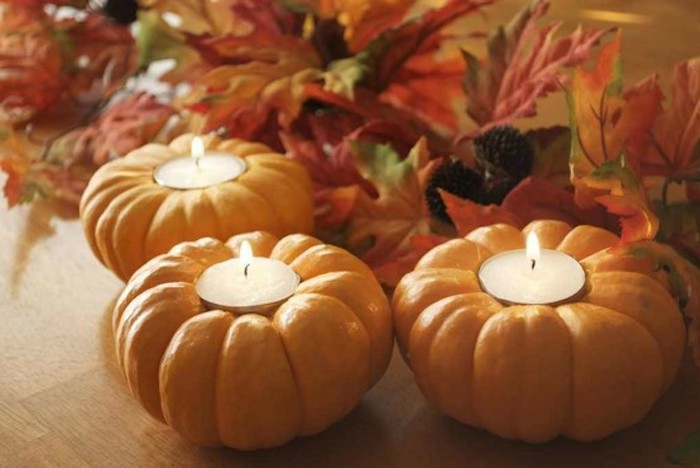 thanksgiving pics, three orange pumpkins wit lit white candles inside, on a wooden surface, colorful autumn leaves in the background