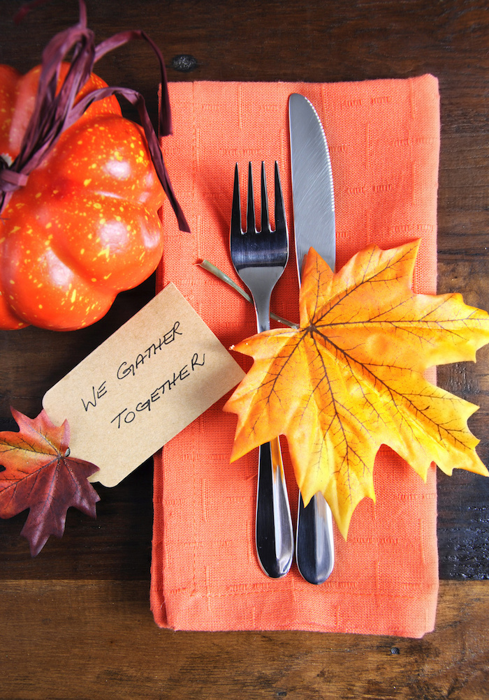 thanksgiving pics, wooden table with an orange pumpkin decoration tied with violet straw cord, next to an orange napkin with silver fork and knife, decorated with a big yellow leaf and a small colorful leaf attached to a piece of paper with a festive message
