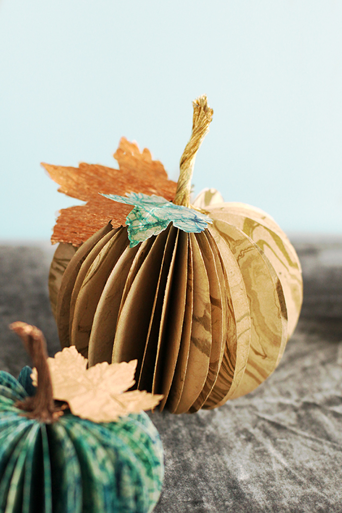 thanksgiving pics paper, paper pumpkins, made from orange and blue paper, with leaf shaped cutouts, on a wooden table