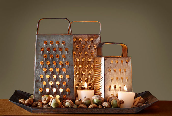 three differently sized cheese graters, lit up from within, placed on a black tray, with green acorns and candles inside and next to them, on a wooden table, dark background