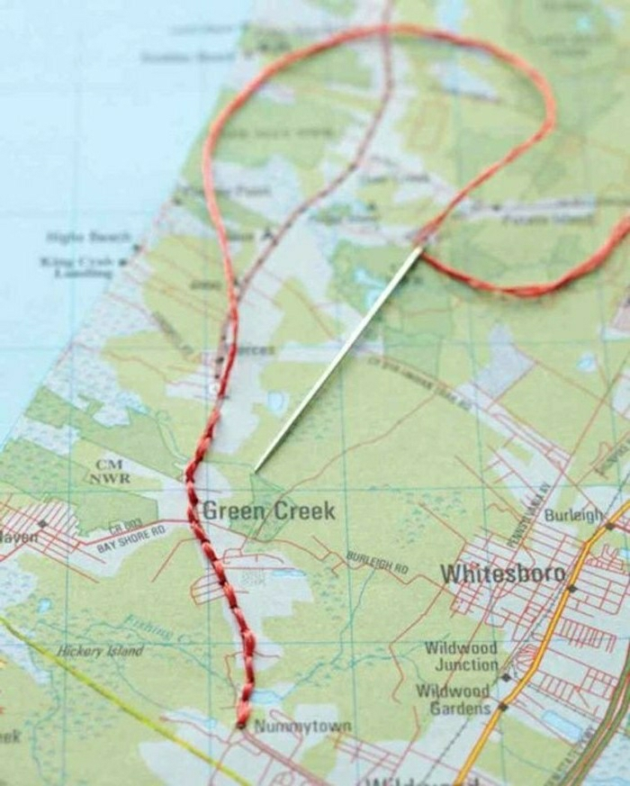 travel journal, close-up of map in light blue and green, with red thread stitched on it, silver needle