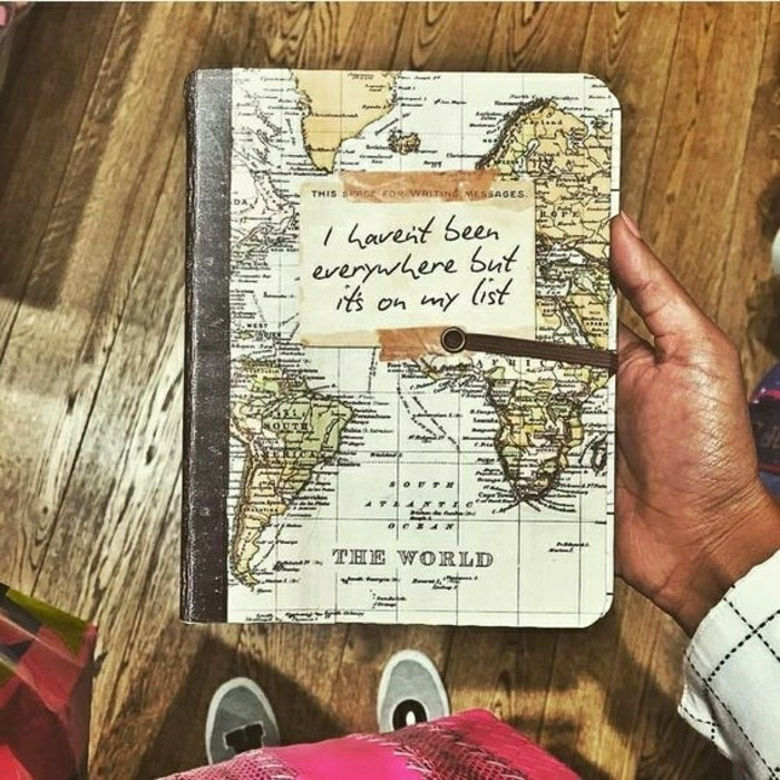 travel journal, a tan hand holding a notebook, with a yellow and green map of the world on the cover, shoes, wooden boards