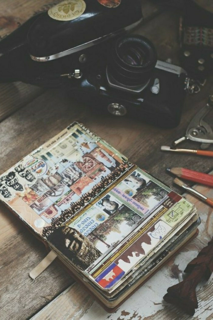 travelogue, wooden surface, open notebook with various photos, cutouts, stickers, drawings, collage,black camera, pencils, paint brushes