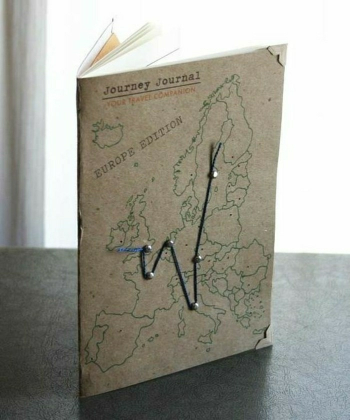 travelogue, light brown notepad with map outlines and blue thread pinned on cover, recycled paper, on dark surface and light background