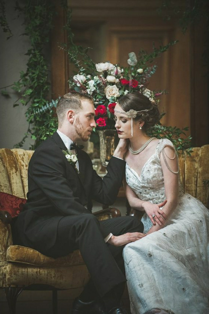 vintage inspired wedding dresses, bride and groom sitting and hugging on a yellow couch, woman wears a 1920s style dress with embroidery beads and pearls and a hair ornament, man wears black suit, flowers in background