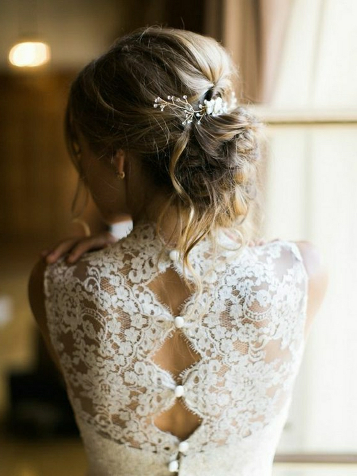 close up of a blonde bride facing backwards, wearing her hair in a messy bun with white ornaments, and a white dress with button up back made of sheer lace