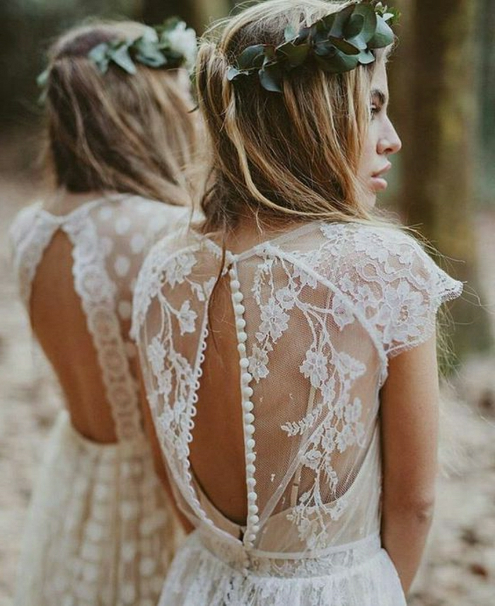 unique wedding dresses, blonde bride with green leaf-crown facing sideways, in a white lace dress with unbuttoned sheer lace back, standing near a mirror