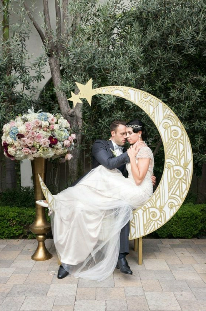 woman in flowing white bridal gown with lace and tulle, sitting on a moon-shaped ornament, hugged by a man in a dark grey suit, near a large vase with flowers, trees in background
