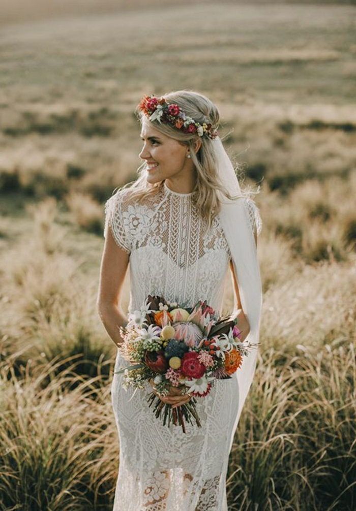 smiling bride with free-falling shoulder-lenght blonde hair, looking sideways, standing in a yellow field, dressed in a white long partly see-through dress with lace, holding a colorful bouquet and wearing a flower crown attached to a veil