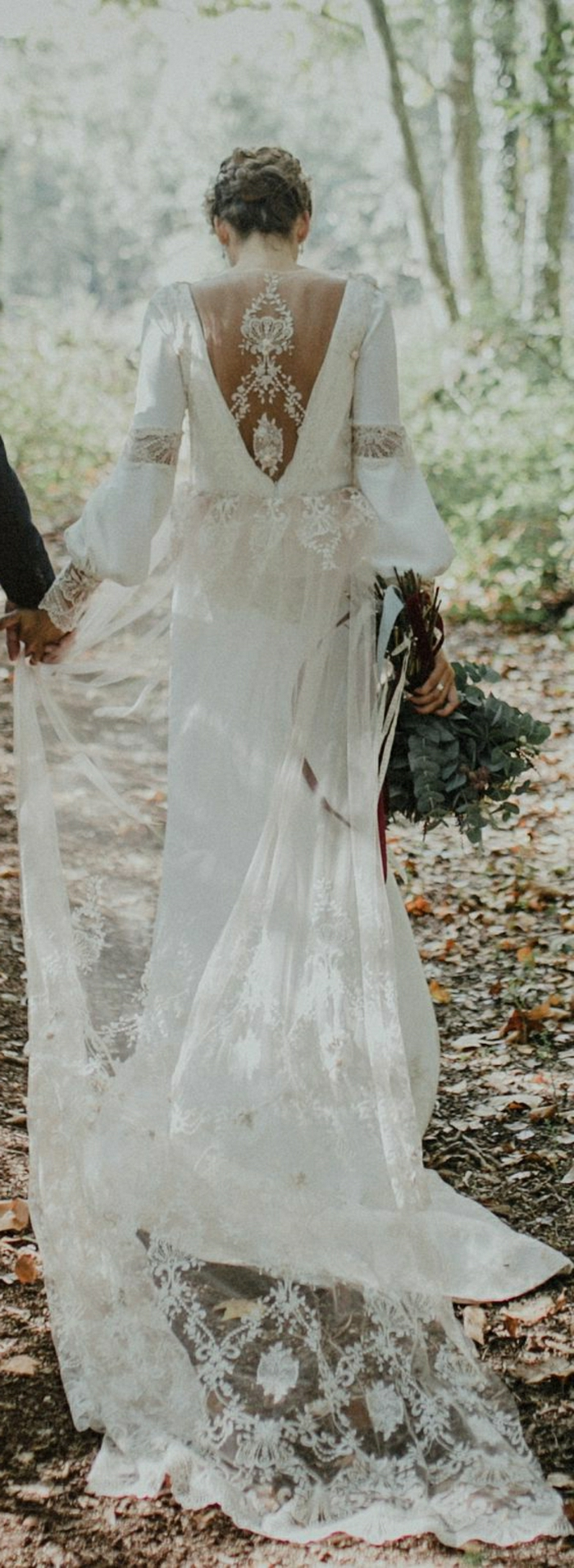 long white bohemian wedding dress with wide sleeves, cutout lave back and long veil, worn by a brunette with a fancy hairdo, holding a man's hand and a bouquet of flowers, woodland background