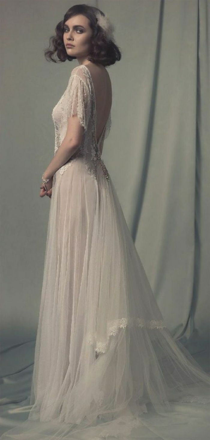 vintage inspired wedding dresses, young woman with 1920s style hair and a white hair ornament, wearing a long white embroidered wedding dress with low back and lace details