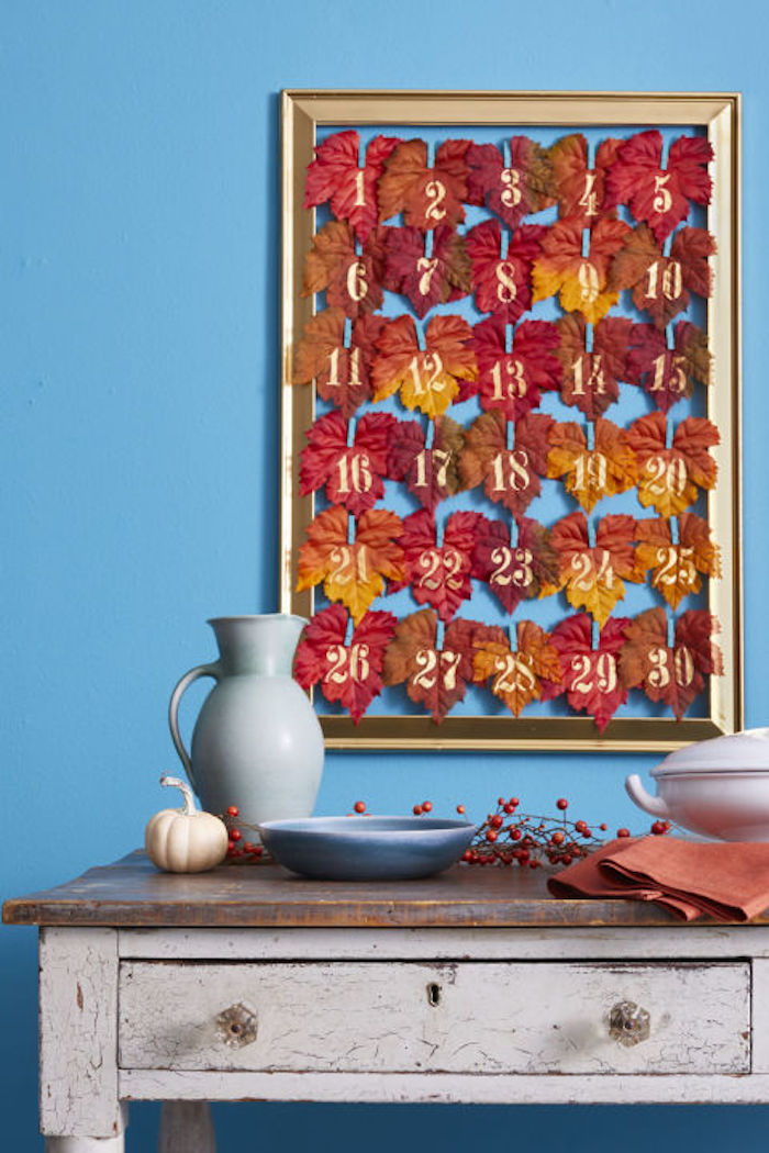 golden frame containing thirty numbered, colorful autumn leaves, hung on a blue wall, near a white and brown antique table with a drawer, blue pitcher and plate, brown dish, orange napkins, a small pumpkin and decorative berries on a twig