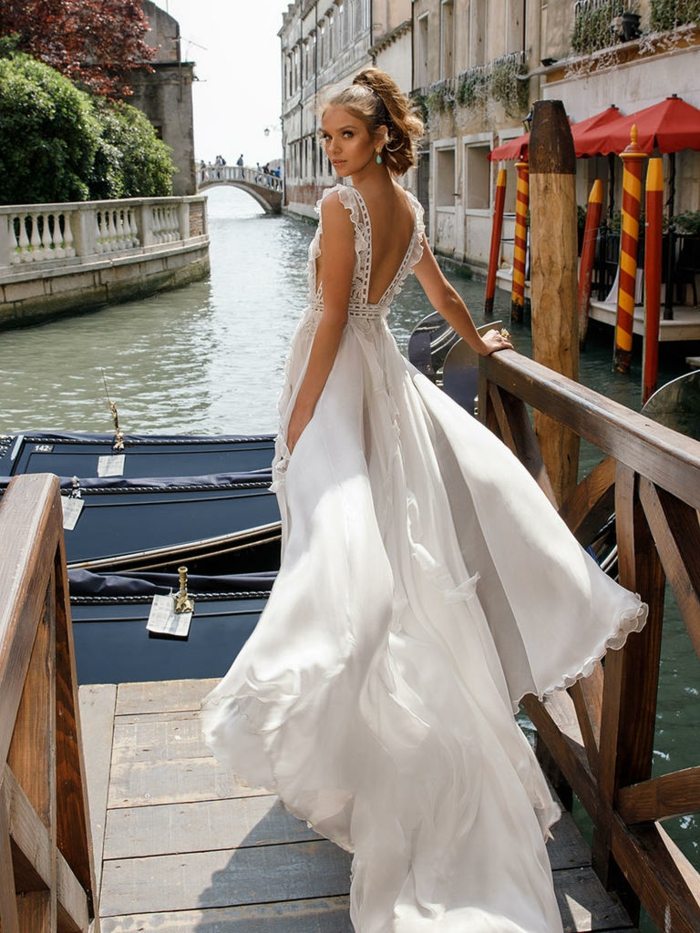 vintage wedding dresses, young bride with tied back hair, standing on quay in Venice near boats and a bridge, long white dress floating in wind, with lace details
