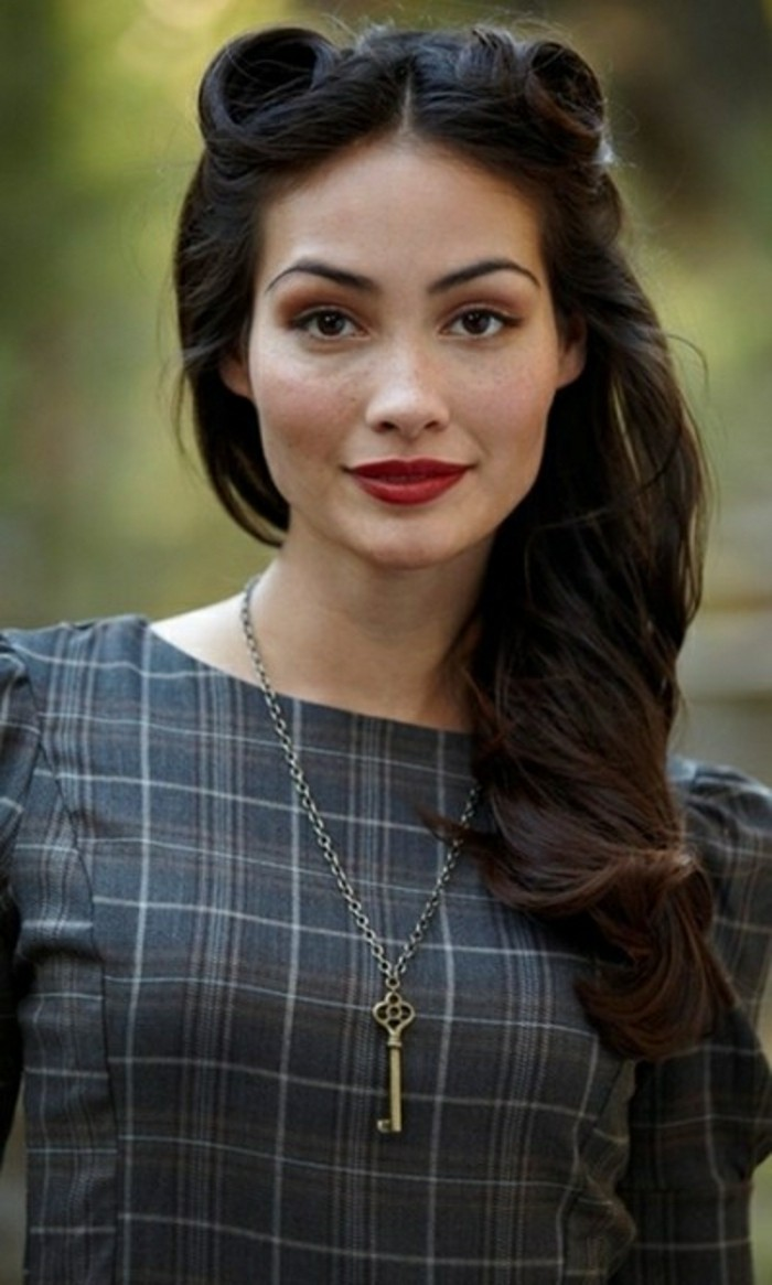 pinned up hairstyles for long hair, woman with victory rolls and long wavy dark hair, black eyes red lipstick and brown eye shadow with fake eyelashes and mascara, tartan top with ruffles and a key pendant