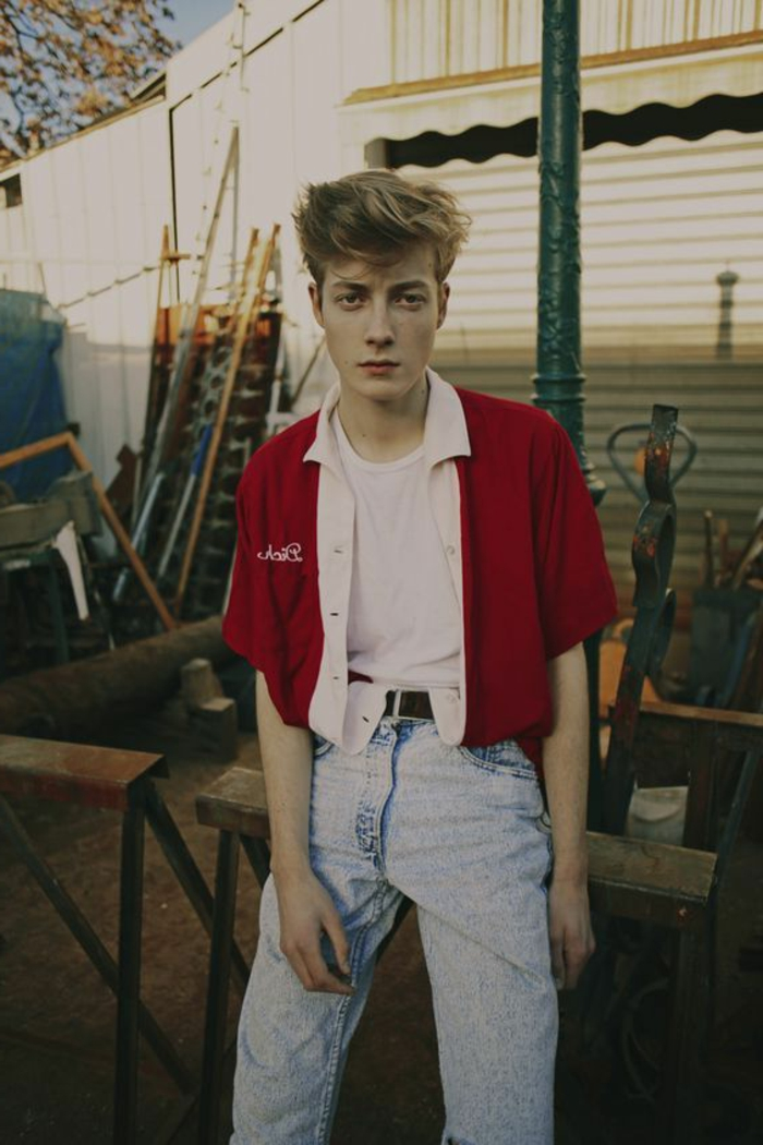 80's fashion for men, blonde boy with gelled up messy hair, wearing white t-shirt and red jacket with cropped sleeves, light blue acid wash jeans, messy yard in background