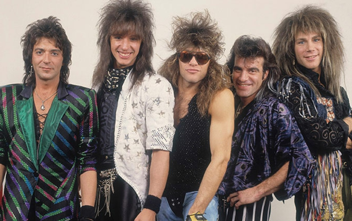 80's fashion for men, bon jovi glam rock band, five men with punk hairstyles and 80s clothing, shiny over-sized blazers with stripes and stars, tassels animal prints jewelry and sunglasses