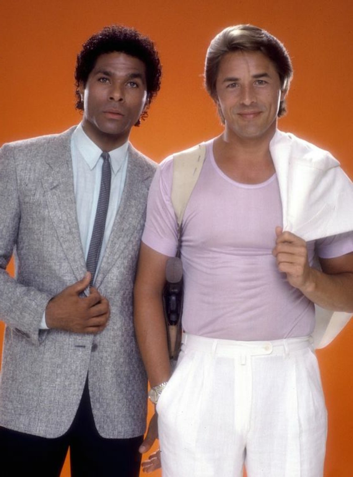 80s clothing, Miami Vice tv show style, African-American man in suit with thin tie, grey blazer and black trousers with white shirt, Caucasian man in pink t shirt with white trousers, holding white blazer over his shoulder