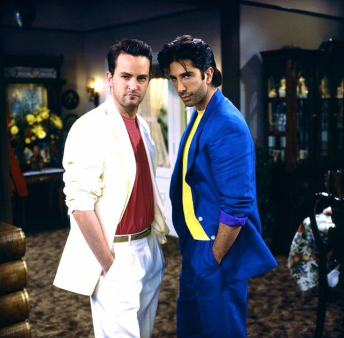 throwback outfits, Matthew Perry and David Schwimmer as Chandler and Ross from Friends, wearing white suit with red t-shirt and blue suit with yellow t-shirt, hands in pockets