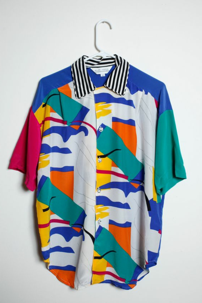 throwback thursday outfits, over-sized white shirt with cropped sleeves and geometrical patters in green orange and red, with striped collar and blue scribbles, on white hanger and white background