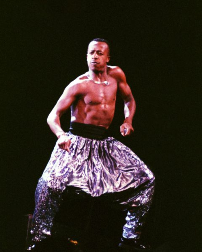 80's hip hop fashion, topless African-American man dancing, wearing shiny baggy parachute pants with wide black belt