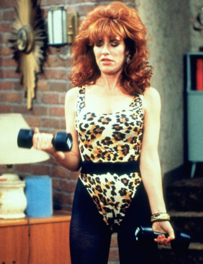 married with children sitcom, katey sagal as peggy bundy, big red permed hair with bangs, wearing animal print body suit with black leggings and belt, lifting weights in livingroom
