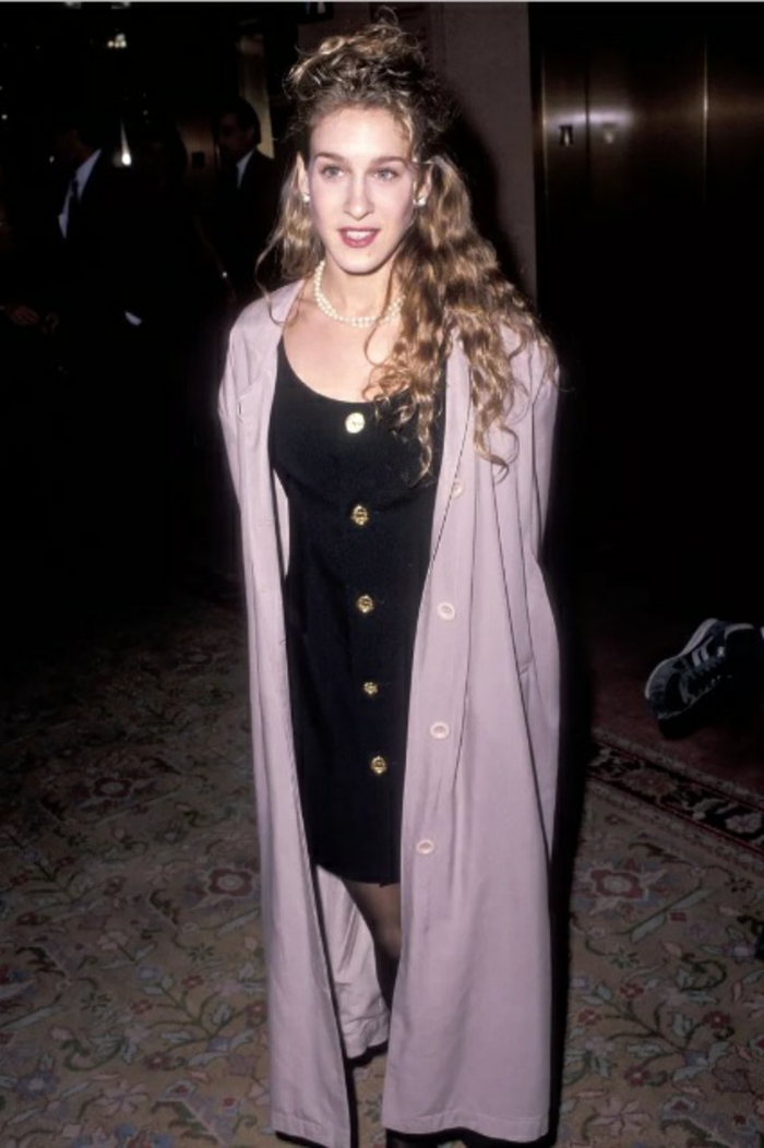 80s fashion trends, young woman Sarah Jessica Parker with long curly blonde hair, pearl necklace and long pale pastel pink jacket, black mini dress with buttons