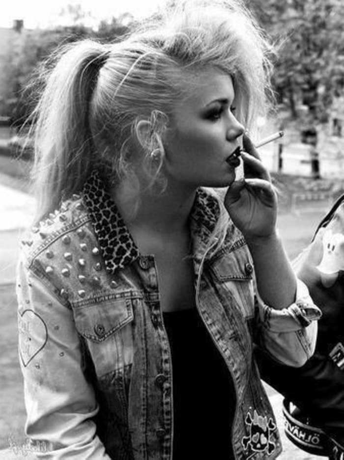 80s fashion, punk girl in black and white photo, heavy make up and smoking a cigarette, studded denim jacket with animal print collar and black top, park and trees in the background