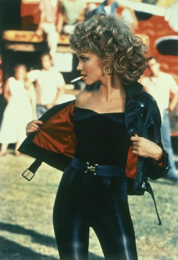 80s fashion trends, Grease,Olivia Newton-John, big curly blonde hair perm, black top and shiny black leggings, black leather jacket with red lining, wide belt and a cigarette