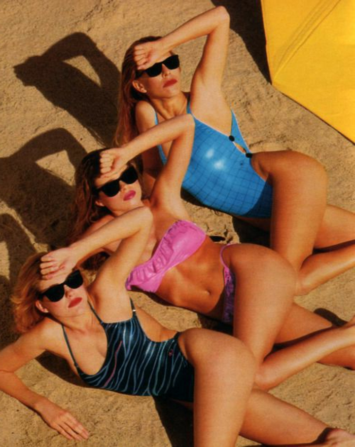 throwback thursday outfits, three blonde women in retro bathing suits, in the same pose lying on sand, wearing sunglasses and shielding themselves from the sun