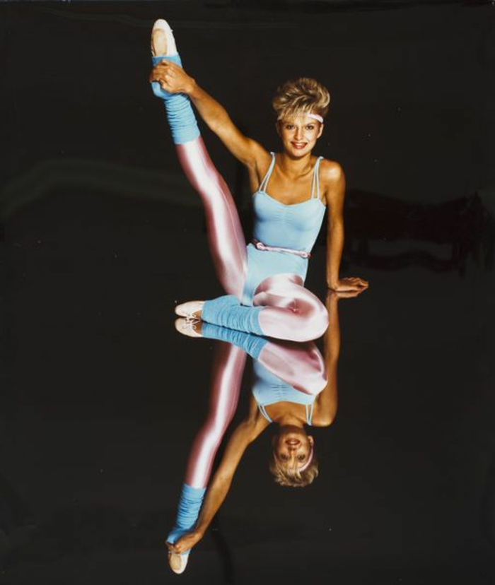 80s fashion trends, smiling blonde woman with short hair, wearing light pastel blue body suit and legwarmers, shiny pink leggings belt and headband