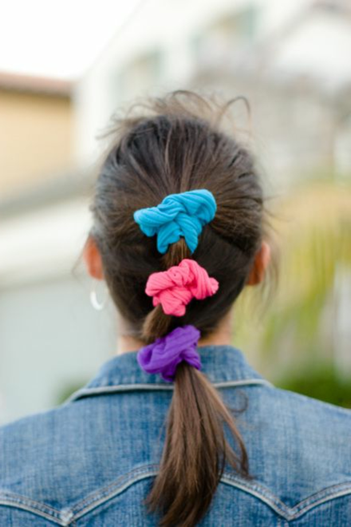 80s clothing, woman facing backwards with brown mid-length hair tied in ponytail, three bright neon scrunchies in blue pink and purple, jeans jacket and smudged background