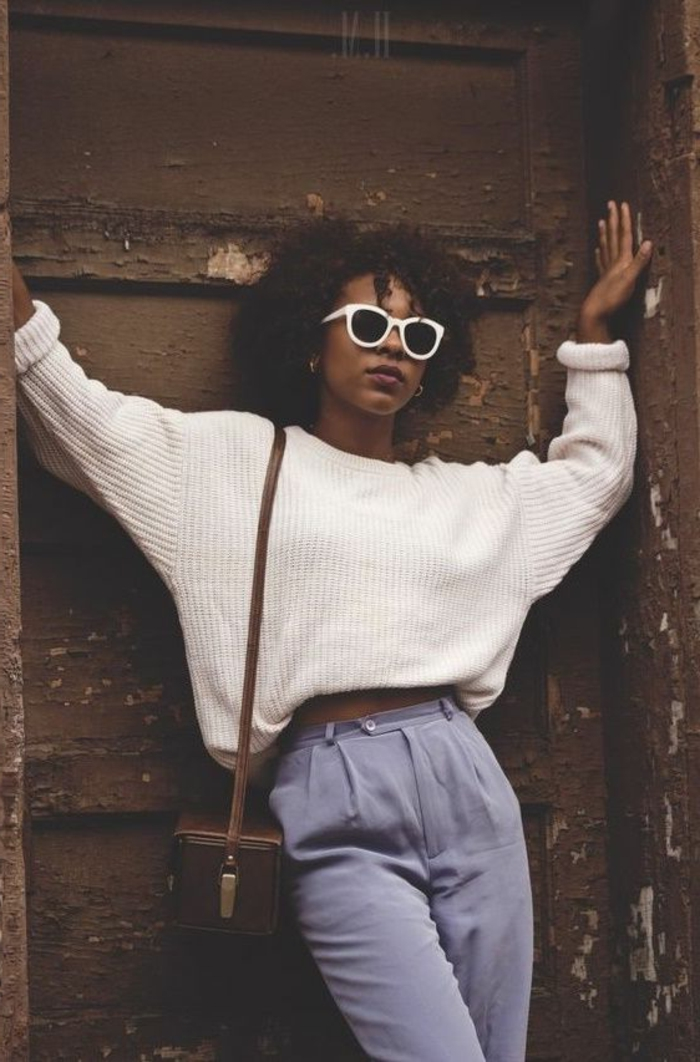 80s fashion, african-american girl leaning on old door, with black curly hair and brown bag, white ribbed sweater with rolled-up sleeves, sunglasses with white plastic frames, pale lilac carrot pants
