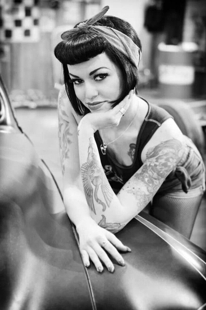 pinup hair, woman with short black hair tied with bandanna and rolled bangs, leaning on vintage car, many tattoos on arms and body